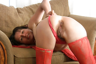 Sexy older women Carmen pulls her sexy red lingerie down around her ankles and finger bangs her moist hairy pussy on the sofa.
